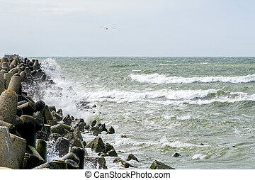 view of the stormy sea, waves splashing against the concrete pier