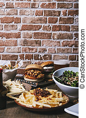 View of the table with a variety of dishes, hamburgers, french fries and salad, drinks and sauce on the wooden table. Restaurant menu. Vertical image