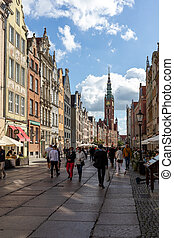View of the Town Hall and tourists and local people strolling on the Long Lane at the Main Town in Gdansk