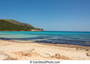 View of the turquoise Mediterranean Sea and the beautiful sandy beach of Cala Agulla on the Spanish holiday island Mallorca