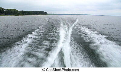 View of the waves behind the speed boat while cruising by the lakeshore