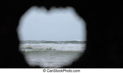 View of the waves breaking through a hole - View of the...