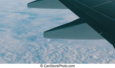 View of the wing of an airplane in flight over beautiful air...