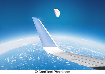 View of the wing of the plane and the moon through the window in the air in flight