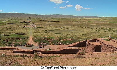 Wide high angle panning shot of Tiwanaku landscape and ruins with visitors at the site. , La Paz, Bolivia