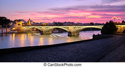 View Of Triana Bridge In Seville Spain At Sunset - The ...