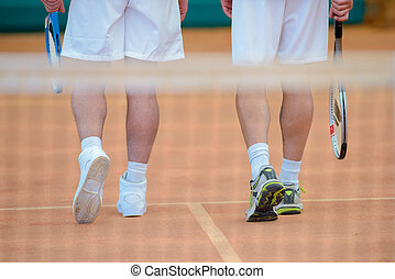 View of two men's legs on tennis court