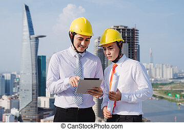 View of Two workers working outside with a tablet on a construction site
