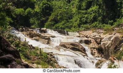 view of waterfall cascade among rocks in tropical park