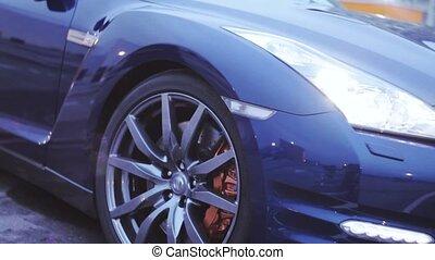 View of wheels iron disk of dark blue new car. Presentation. Headlight. Sun. Automobile. Cold shades
