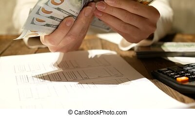 View of woman hands counting dollar bills.