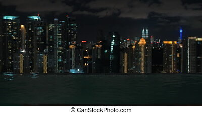 View of woman swimming in the pool on the skyscraper roof against night city landscape. Kuala Lumpur, Malaysia