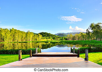 View of wooden bridge water forest mountain natural landscape with blue sky background in Thailand.
