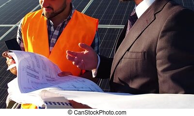 View of worker and businessman discussing project, solar panels behind them.
