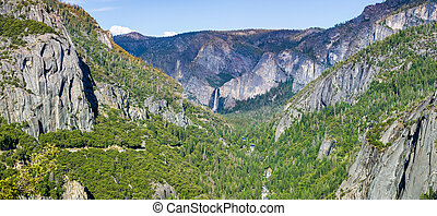 View of Yosemite Valley with Merced river flowing through evergreen forests and Bridalveil Falls visible in the background; Yosemite National Park, Sierra Nevada mountains, California