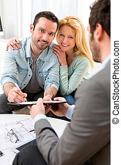 Young attractive couple signing contract with real estate agent