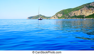 view on a coast with a mountain chain and a boat in the mediterranean sea on the island corfu (nearby town Afionas)