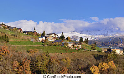 view on alpine village in a hill and snowy mountain background