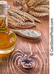 view on bottle of oil wooden spoon with flour ears wheat o