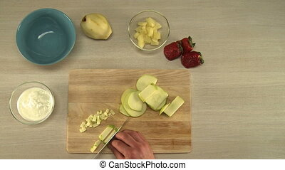 View on chef cutting apple for fruit salad