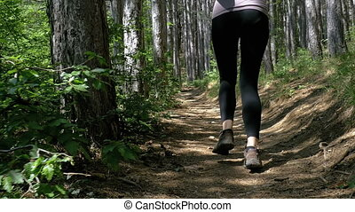 View on Feet of Traveler Woman Hiking Running on the Forest Trail Path in Mountain