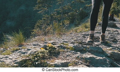 View on Feet of Traveler Woman Hiking Walking on the Top of Cliff in Mountain. Slow Motion
