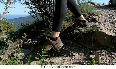 View on Feet of Traveler Woman Hiking Walking on the Top of Cliff in Mountain. Walking on Rocks
