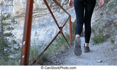 View on Feet of Traveler Woman Hiking Walking on Trail Path in Stone Mountain. Camera follow hikers legs