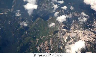 View on landscape of mountains and clouds from window of flying plane