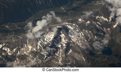 View on landscape of mountains from window of flying plane