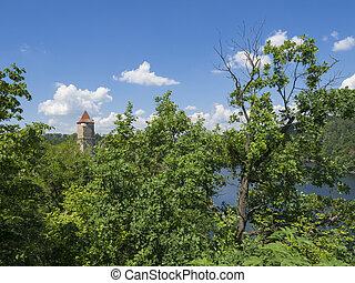 view on medieval czech castle Zvikov round tower and river Vltava, green trees in foreground blue sky, white clouds background