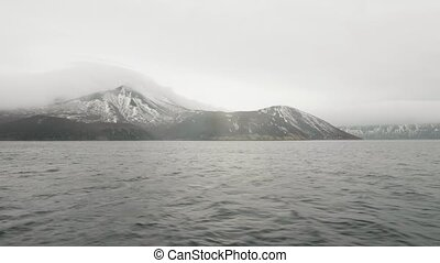 View on mountain with snowy peaks and sea. Sea ship sailing...