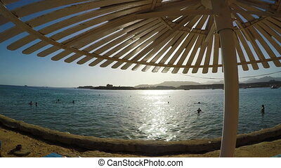 View on sea and beach in hot summer day with wooden umbrella