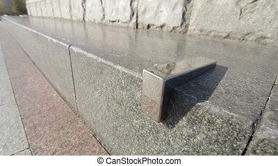 View on Skatestopper or anti-skate device on street granite ledge on monument