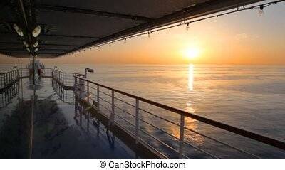 view on sunset from deck of cruise ship moving