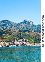 view on Taormina - tourist resort on mountain and Giardini...