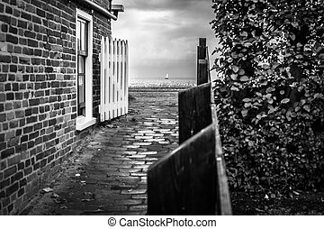 View on the high seawall from an old dutch fishing village on the IJsselmeer. Sailing Boat is passing the coast.