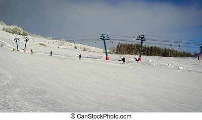 View on the long ski lift at the hill for skiing. Skiers...