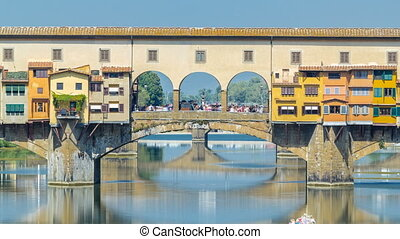 View on The Ponte Vecchio on a sunny day timelapse, a medieval stone segmental arch bridge over the Arno River, in Florence, Italy