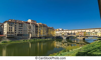 View on The Ponte Vecchio on a sunny day timelapse hyperlapse, a medieval stone segmental arch bridge over the Arno River, in Florence, Italy