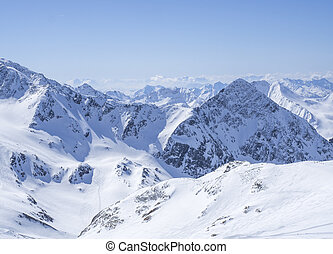 View on winter landscape from the top of Schaufelspitze mountain at Stubai Gletscher ski area with snow covered peaks at spring sunny day. Blue sky background. Stubaital, Tyrol, Austrian Alps
