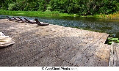 View on wooden pier with loungers in summer calm day