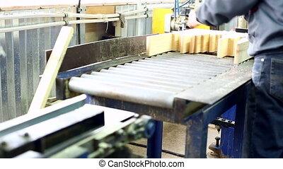 View on worker puts glued lamellas in machine - Woodworking...
