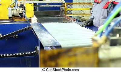 View on worker takes glued lamellas from machine -...
