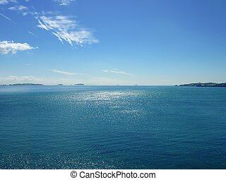View onto the blue sea of the Hauraki Gulf near Auckland with islands and peninsulas in the background