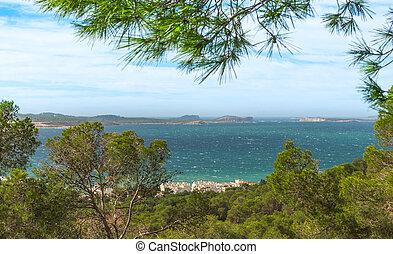 View out to sea through naturally framing trees.  San Antonio Sant Antoni de Portmany in the Balearic Islands, Ibiza.