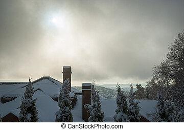 View over rooftops and chimneys in snow, Holmenkollen, Oslo, Norway