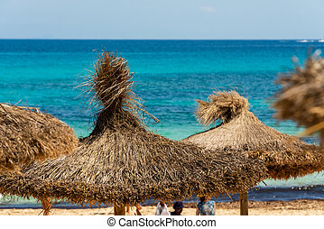 View over straw parasols from the beach Cala Agulla to the turquoise Mediterranean Sea on the Spanish holiday island Mallorca