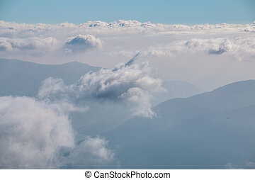 View over the clouds in the sky with mountains in the background