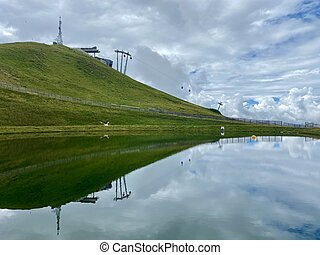View over water reservoir used for snow cannons in winter in the skiing region of Hinterglemm in the Austrian alps on a summer day with great mountain panorama in the background